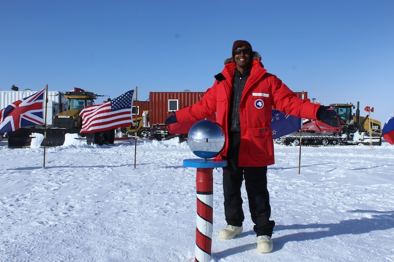 Capt. Michael Nayak, an AFRL scientist, at the Ceremonial South Pole with the South Pole Traverse (SPT) in the background. Several groups of trucks, bulldozers and Sno-Cats (tracked vehicles for snowy conditions) pull massive sleds with supplies from McMurdo Station to the South Pole Station. Each sled holds 20,000 gallons, or 140,000 pounds, of jet fuel. Every year, workers rebuild the thousand mile-road that supports this journey. (Courtesy photo)