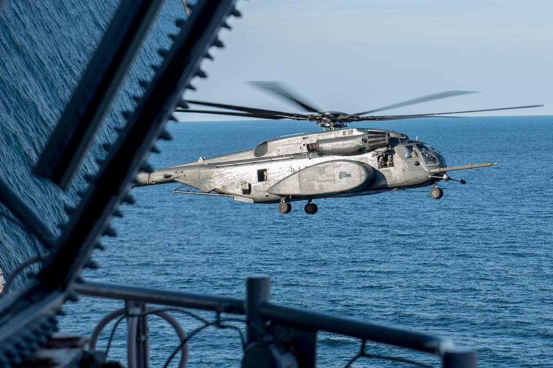 A helicopter prepares to land aboard an aircraft carrier.