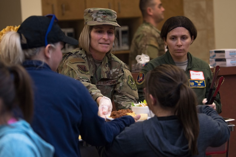 Col. Tiffany Morgan, 23d Medical Group commander, sets a plate on a tray during a deployed spouses dinner, Jan. 15, 2019, at Moody Air Force Base, Ga. The mission's success depends on resilient Airmen and families who are prepared to make sacrifices with the support of their fellow Airmen, local communities and leadership. (U.S. Air Force photo by Airman Taryn Butler)