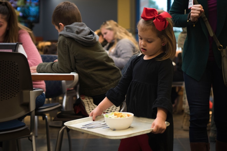 A guest carries her tray during a deployed spouses dinner, Jan. 15, 2019, at Moody Air Force Base, Ga. The mission's success depends on resilient Airmen and families who are prepared to make sacrifices with the support of their fellow Airmen, local communities and leadership. (U.S. Air Force photo by Airman Taryn Butler)