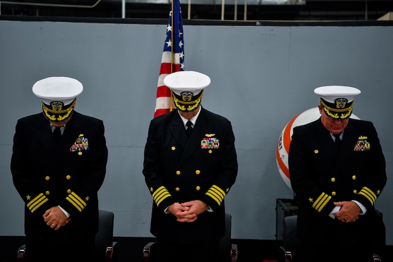 From left, Cmdr. William Edenbeck, Navy Munitions Command Atlantic Unit Charleston commanding officer, Capt. Jake Jacobs, Navy Munitions Command Atlantic commander, and Cmdr. Patrick Sutton, former NMC commanding officer, bow their heads during the closing benediction of their change of command ceremony Jan. 16, 2018.