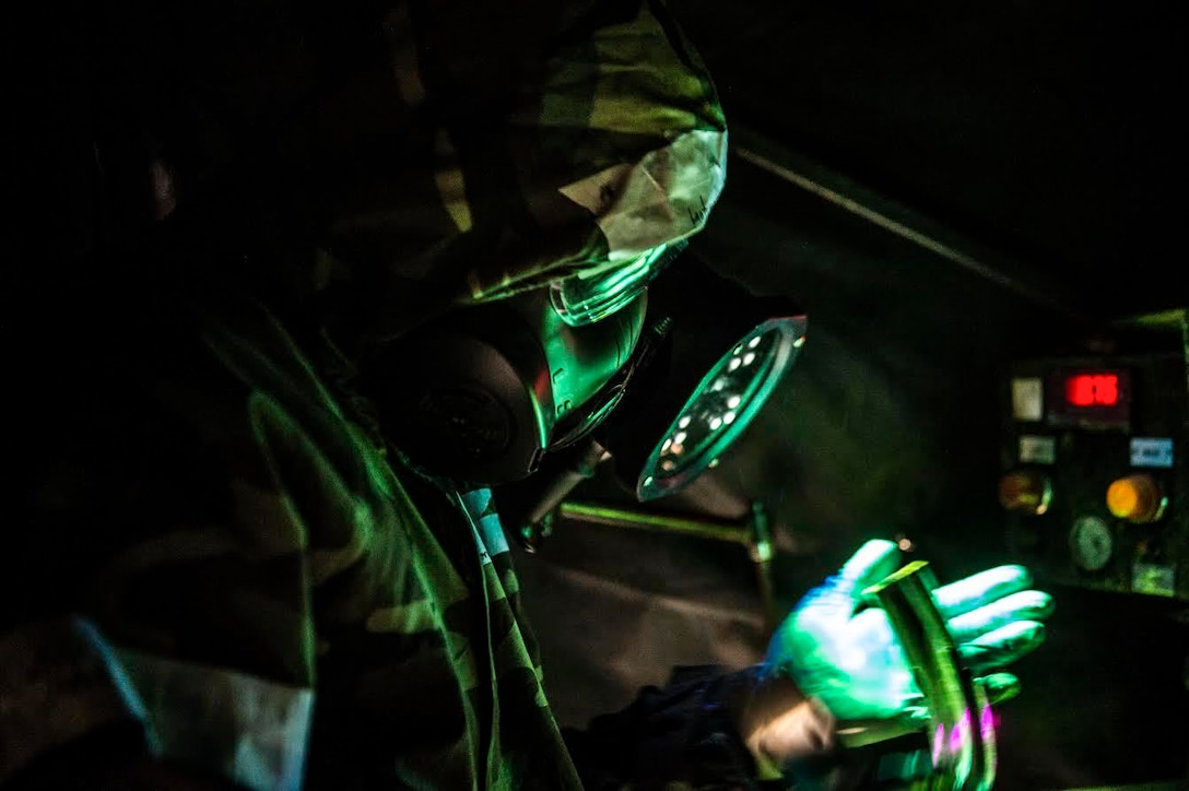 An airman dressed in protective gear inspects a part.