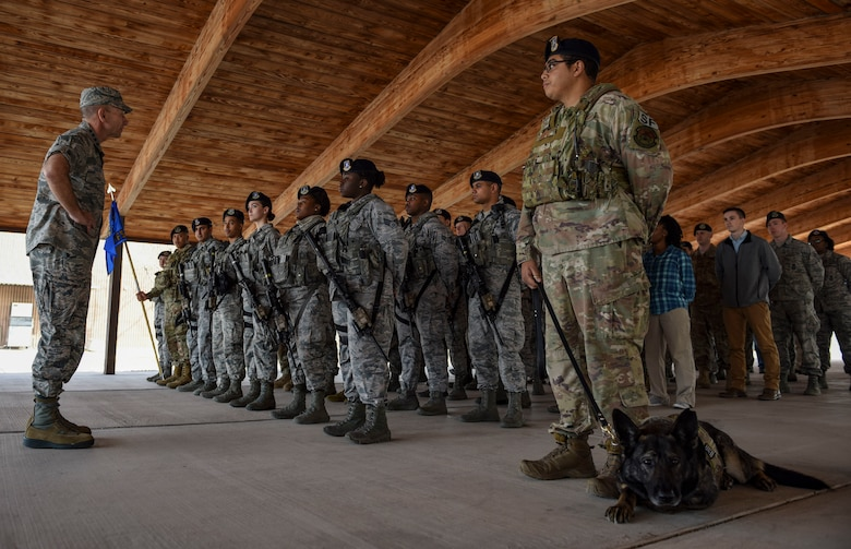A flight of Airmen stand at parade rest.