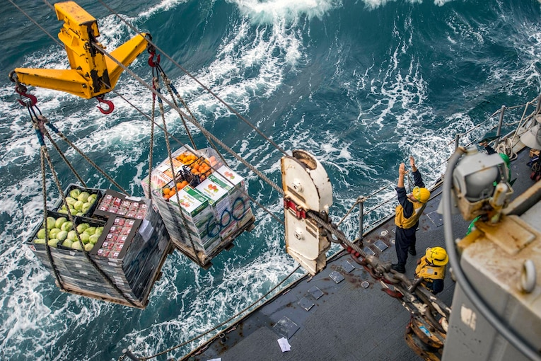Sailors receive pallets of supplies across a line.