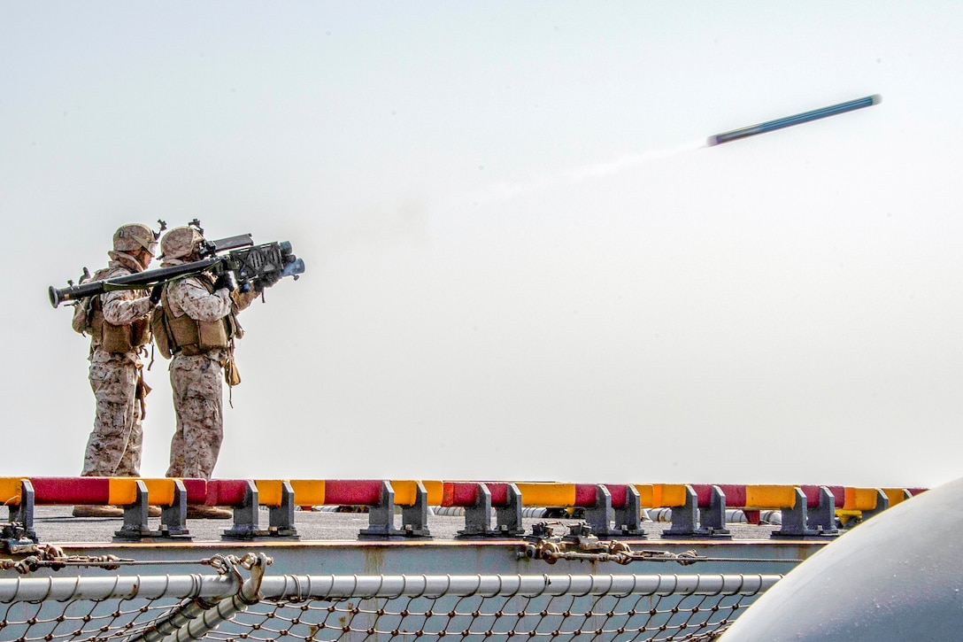 Two Marines fire a stinger missile from the deck of a large naval ship.