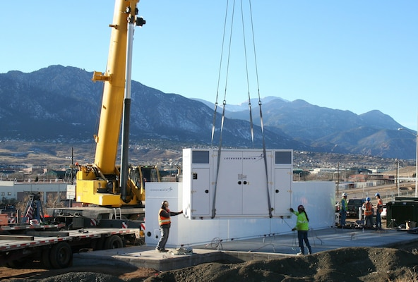 Workers install portions of the 8.5 megawatt-per-hour battery system at Fort Carson, Colorado. Huntsville Center's Energy Savings Performance Contracting program coordinated the project designed to reduce peak electricity use costs, especially during the summer cooling season.