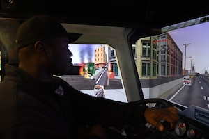 Jonathan Matthews, a firefighter assigned to the 97th AMW Fire Department, drives a firetruck driving simulator Jan. 15, 2019, at Altus Air Force Base, Okla. The simulator comes with scenarios built in, but can also be customized for brand new scenarios, allowing firefighters to hone their skills in a variety of situations. (U.S. Air Force photo by Airman 1st Class Jeremy Wentworth)