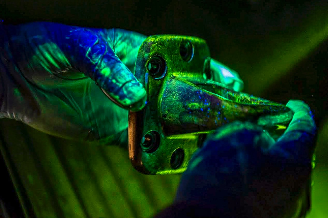 An airman looks at a piece of hardware under a blacklight.