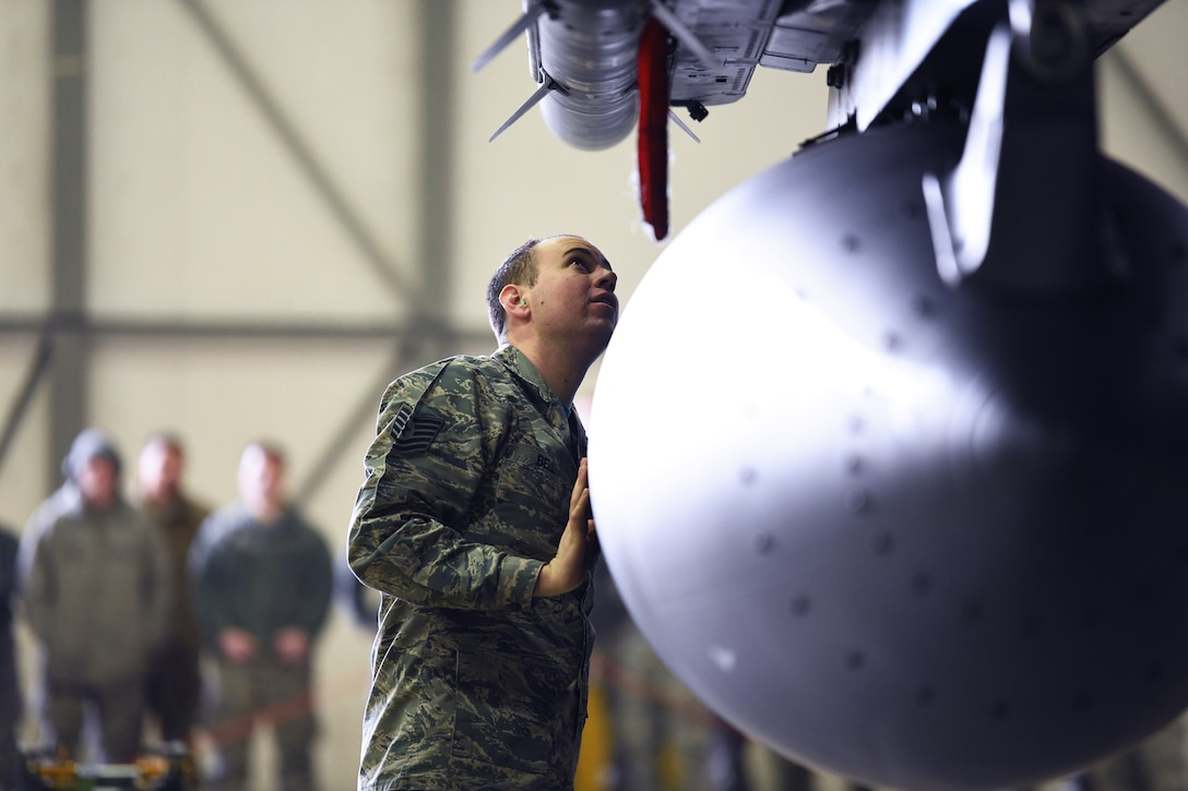 A loading standardization crew member reviews the work of a load crew team at a weapons loading competition at Royal Air Force Lakenheath, England, Jan. 18, 2019. The 3-person teams representing the 492nd, 493rd and 494th Aircraft Maintenance Units, raced against the clock to see who could complete their tasks safely and with accuracy. (U.S. Air Force photo by Airman 1st Class Shanice Williams-Jones)