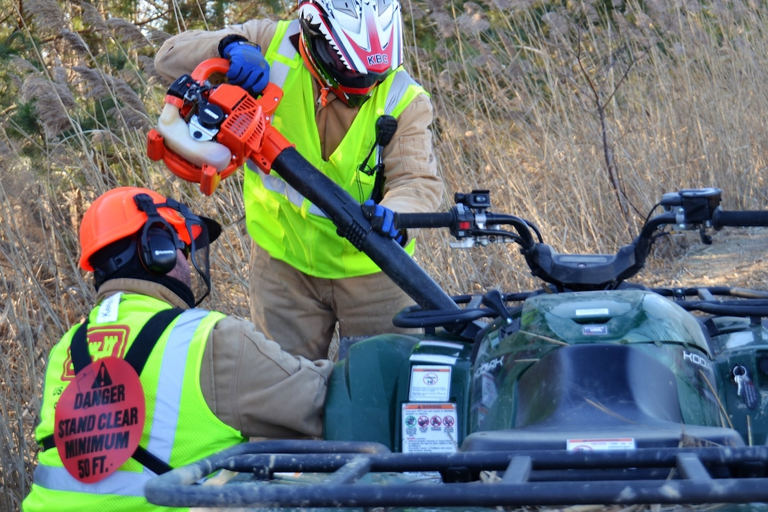 Two men in safety vests and helmets use a leaf blower to clean off an all-terrain vehicle on a levee covered with phragmites.