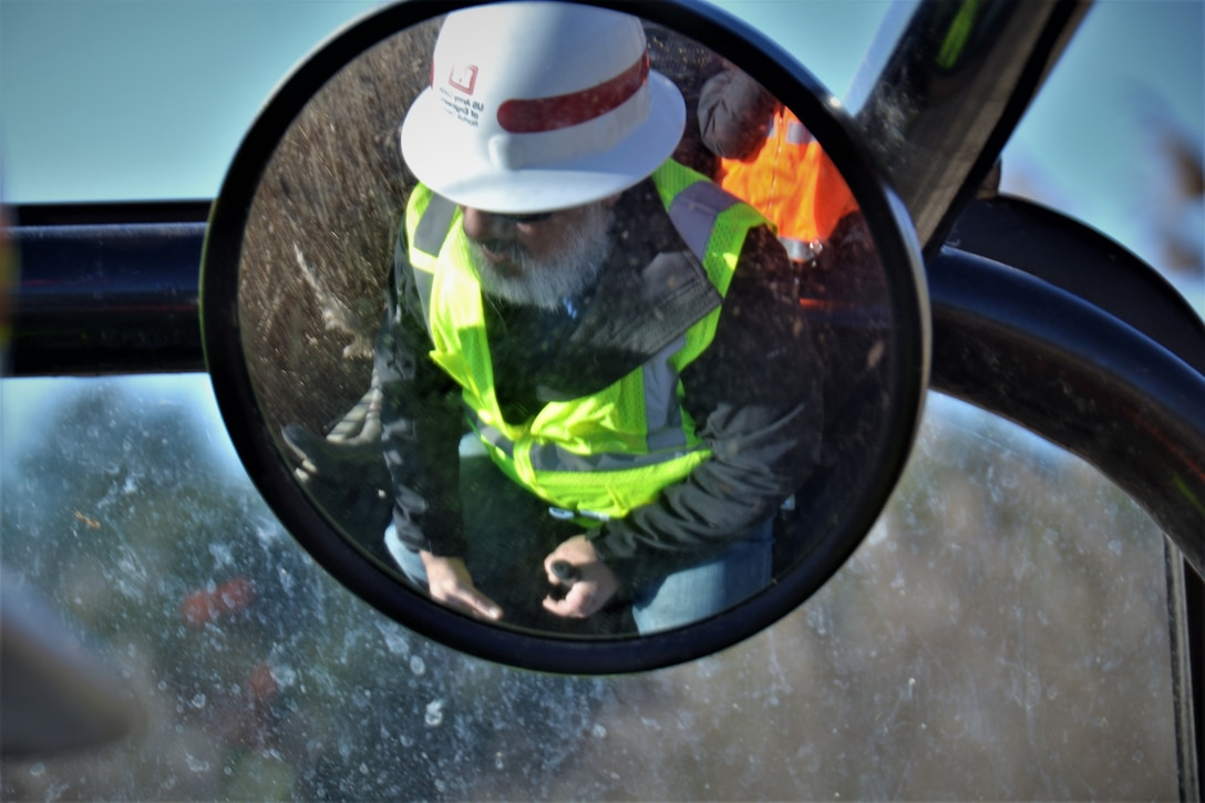 The reflection of a man with a hard have and reflective vest in seen in the mirror of an all-terrain vehicles as he drives it.