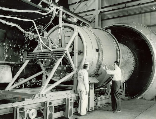 A full-scale replica of the Gemini adapter section and base of capsule is being prepared for simulated high altitude test of emergency abort system occurring in 1963 in the AEDC J-1 test cell at Arnold Air Force Base. The linear shaped explosive charge, which encircles the adapter section (the larger right-hand portion of this test installation), is set off to free the capsule from the booster, then the capsule retrorockets are fired to push the capsule away from the booster. The test showed modifications are needed to provide for successful emergency aborts. (U.S. Air Force photo)