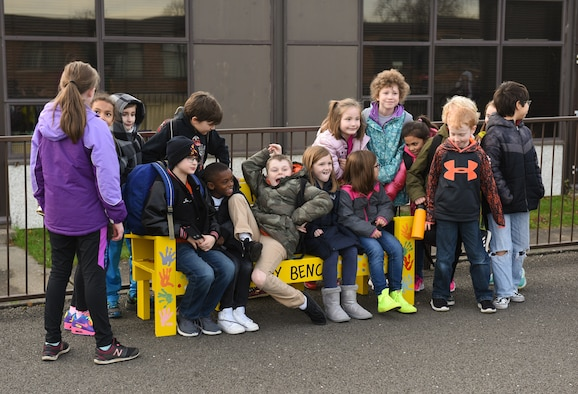 Children at the RAF Alconbury Elementary School sit on the new Buddy Bench at RAF Alconbury, United Kingdom, Jan.15, 2019. The new Buddy Bench has been placed at the base elementary school to promote kindness and healthy relationships within the school system. (U.S. Air Force photo by Airman 1st Class Jennifer Zima)