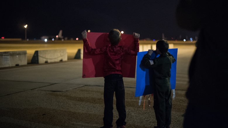 Two boys raise posters for their father returning from a deployment at Barksdale Air Force Base, La., Jan. 16, 2019. Their father is part of the 96th Bomb Squadron that deployed to Andersen Air Force Base, Guam. (U.S. Air Force photo by Airman 1st Class Lillian Miller)