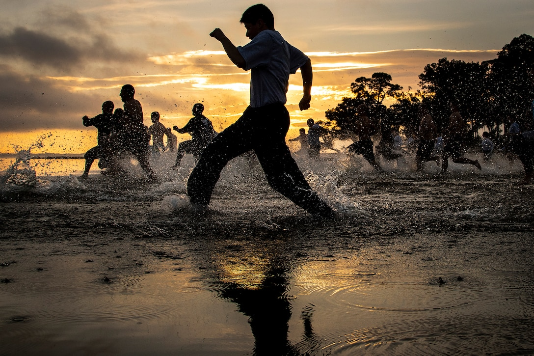 A group of people running in water.