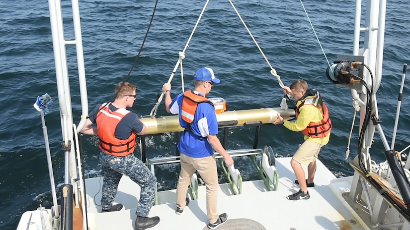Three men on the back of a boat lower an autonomous underwater vehicle into water.