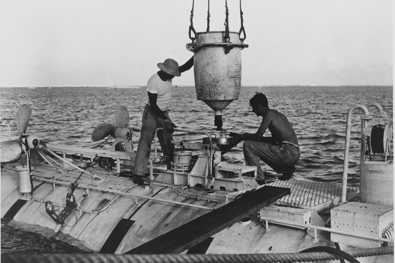 Two men load iron shot ballast into a submersible.