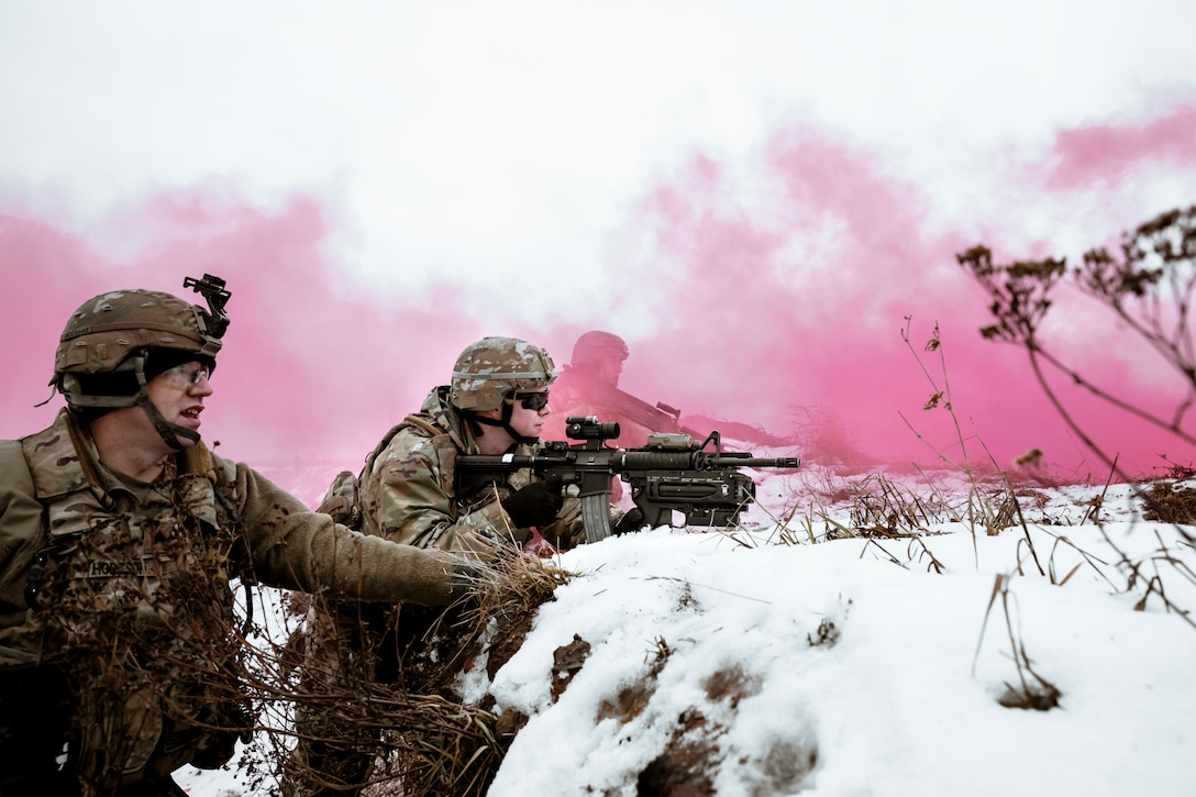 Three soldiers stand behind a snowy mound while one points his weapon.