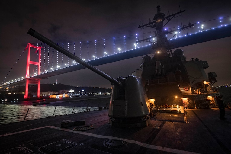 A military ship goes underneath a lit bridge at night.