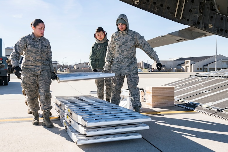 Ramp operations specialists assigned to the 436th Aerial Port Squadron carry the ramp sections of DOMOPS Airlift Modular Approach Shoring Jan. 11, 2019, at Dover Air Force Base, Del. The modular shoring was used to upload five vehicles belonging to the Delaware National Guard's 31st Civil Support Team, Weapons of Mass Destruction headquartered in Smyrna, Del. The vehicles and team members were airlifted by a C-17 to support the Florida National Guard during a large-scale training exercise Jan. 14-18. The 31st CST maintains the capability to mitigate the consequences of any WMD or Nuclear, Biological, and Chemical event, whether natural or man-made. They are experts in WMD effects and NBC defense operations. (U.S. Air Force photo by Roland Balik)