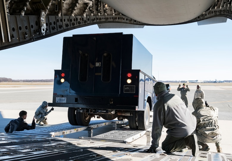 Ramp operations personnel assigned to the 436th Aerial Port Squadron along with 137th Airlift Squadron loadmasters from Stewart Air National Guard Base, Newburgh, N.Y., watch a vehicle back up onto a C-17 Globemaster III using the DOMOPS Airlift Modular Approach Shoring Jan. 11, 2019, at Dover Air Force Base, Del. The modular shoring was used to upload five vehicles belonging to the Delaware National Guard's 31st Civil Support Team, Weapons of Mass Destruction headquartered in Smyrna, Del. (U.S. Air Force photo by Roland Balik)