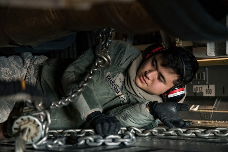 Underneath a vehicle, Airman 1st Class Jacob Vangchhia, 436th Aerial Port Squadron ramp operations specialist, attaches cargo chains to secure a vehicle to a C-17 Globemaster III cargo floor Jan. 11, 2019, at Dover Air Force Base, Del. Vangchhia and other ramp operations personnel loaded five vehicles belonging to the Delaware National Guard's 31st Civil Support Team, Weapons of Mass Destruction headquartered in Smyrna, Del. (U.S. Air Force photo by Roland Balik)