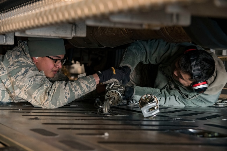 Ramp operations specialists, Airman 1st Class Francisco Garcia Matos, 71st Aerial Port Squadron, Joint Base Langley-Eustis, Va., and Jacob Vangchhia, 436th APS, install cargo chains to secure a vehicle to a C-17 Globemaster III cargo floor Jan. 11, 2019, at Dover Air Force Base, Del. Garcia Matos and Vangchhia, along with other ramp operations personnel loaded five vehicles belonging to the Delaware National Guard's 31st Civil Support Team, Weapons of Mass Destruction headquartered in Smyrna, Del. The 71st APS is a geographically-separated unit of the 512th Airlift Wing, Dover AFB (U.S. Air Force photo by Roland Balik)