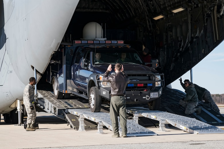 With the assistance of 436th Aerial Port Squadron ramp operations personnel, Staff Sgt. Ryan Stanich, 137th Airlift Squadron C-17 loadmaster, Stewart Air National Guard Base, Newburgh, N.Y., marshals a vehicle backing up on the DOMOPS Airlift Modular Approach Shoring Jan. 11, 2019, at Dover Air Force Base, Del. The vehicles belong to the Delaware National Guard's 31st Civil Support Team, Weapons of Mass Destruction headquartered in Smyrna, Del. The vehicles and team members were airlifted to Florida to support the Florida National Guard during a large-scale training exercise Jan. 14-18. The 31st CST maintains the capability to mitigate the consequences of any WMD or Nuclear, Biological, and Chemical event, whether natural or man-made. They are experts in WMD effects and NBC defense operations. (U.S. Air Force photo by Roland Balik)