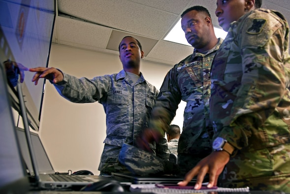 Senior Airman David Daniel, left, with the Maryland Air National Guard's 275th Cyber Operations Squadron, points out key pieces of information on cyber defense operations to Army Maj. Steven Jackson, assistant intelligence officer with with the Mississippi National Guard, and Army Staff Sgt. Nyesha Bradley, with the Louisiana Army National Guard's D Company, 769th Brigade Engineer Battalion, during exercise Cyber Shield 17 at Camp W.G. Williams in Bluffdale, Utah, in April 2017.