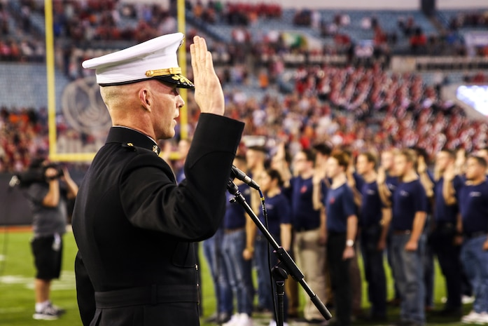 Brig. Gen. James F. Glynn, commanding general of Marine Corps Recruit Depot Parris Island and the Eastern Recruiting Region, swears young men and women into the Marine Corps during the pre-game show of TaxSlayer Gator Bowl, Dec. 31, 2018, at TIAA Bank Field in Jacksonville, Florida. Glynn was invited by the Jacksonville Sports Council to be the guest-of-honor during the game. (U.S. Marine Corps Photo by Cpl. Mike Hernandez)