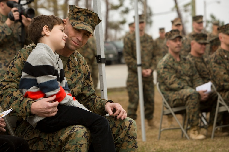 A young boy sits on the lap of his father.