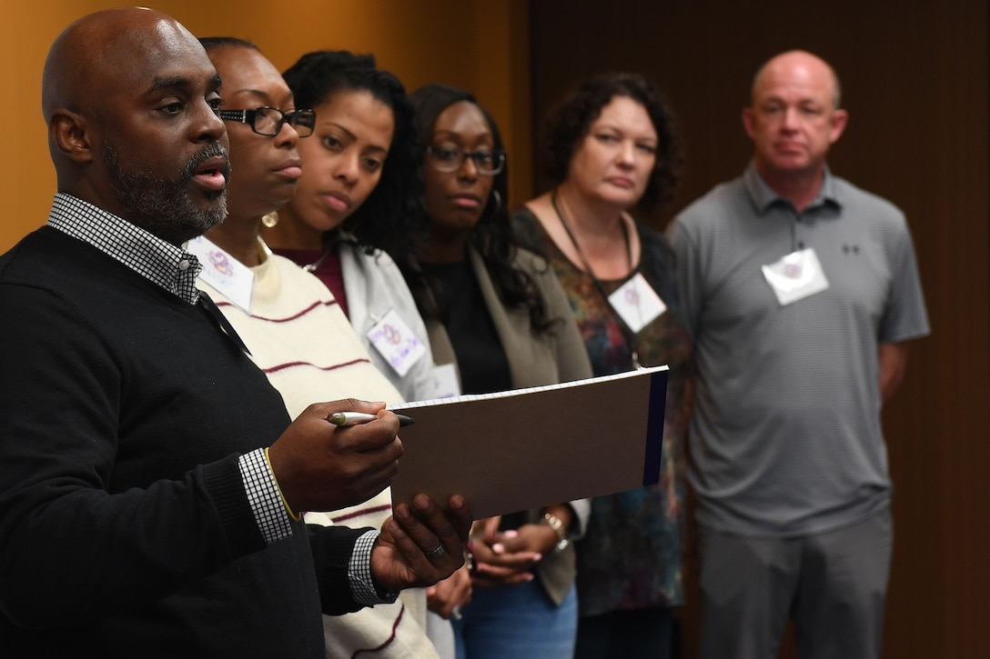 Six people stand up in the front of a room speaking.