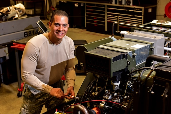 Man holding socket wrench working on equipment smiling at camera