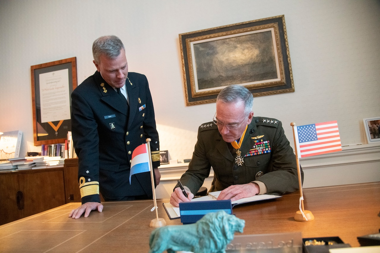 Joint Chiefs chairman signs guest book in The Hague, Netherlands