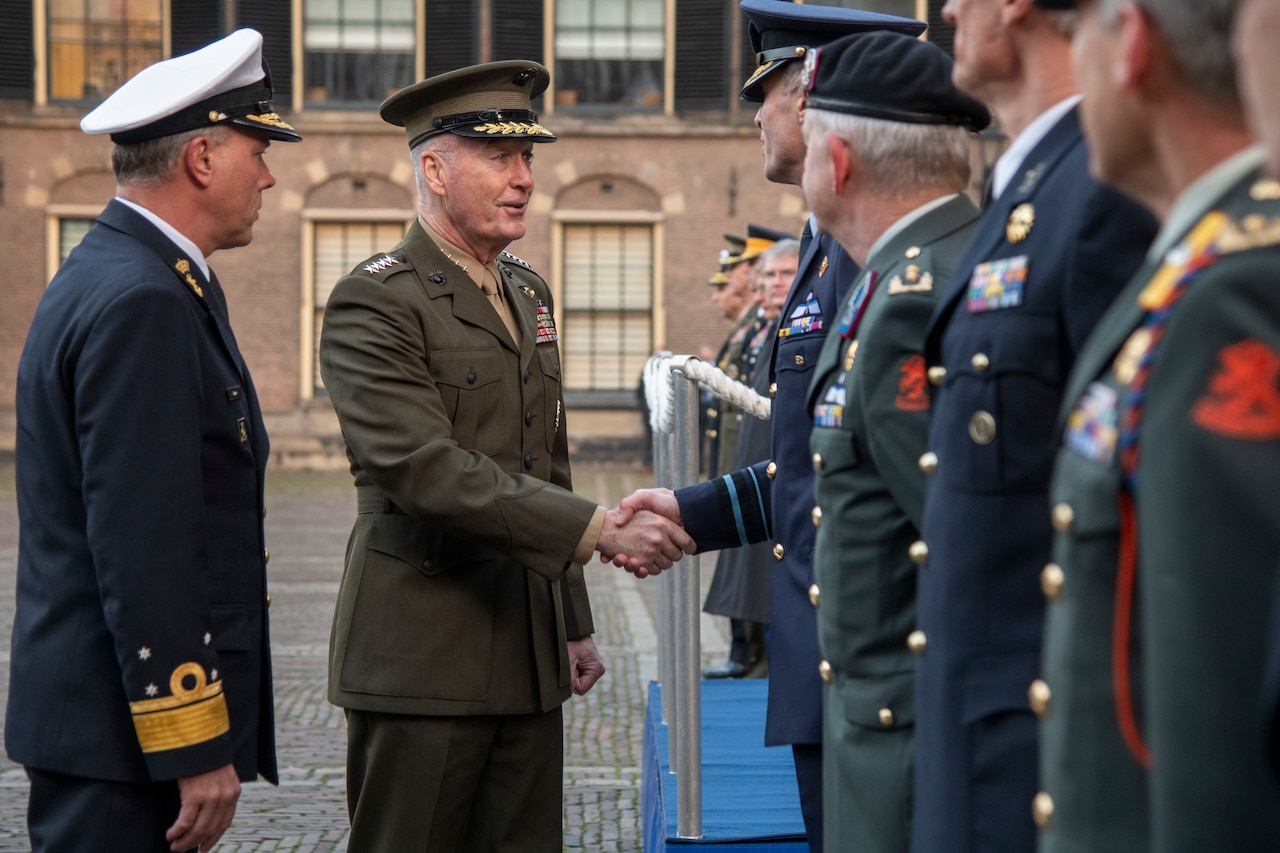 Joint Chiefs chairman shakes hands with a man standing with a group of other men.