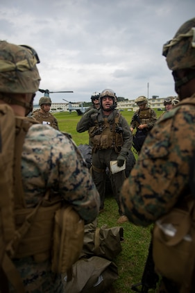 An MV-22B Osprey crew chief gives a safety brief to landing support specialists during helicopter support team training at Camp Foster, Okinawa, Japan, Jan. 14, 2019. Landing Support Company, 3rd Transportation Support Battalion, Combat Logistics Regiment 3, 3rd Marine Logistics Group supported Marine Medium Tiltrotor Squadron 265, Marine Aircraft Group 36, 1st Marine Aircraft Wing during external lift training, which ensures pilots and landing support specialists are able to communicate as well as transport gear from one location to another. (U.S. Marine Corps Photo by Cpl. André T. Peterson Jr.)