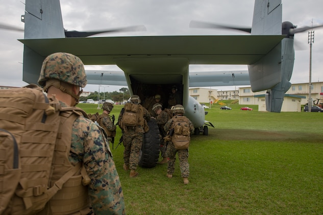Landing support specialists roll a Medium Tactical Vehicle Replacement tire onto an MV-22B Osprey during helicopter support team training at Camp Foster, Okinawa, Japan, Jan. 14, 2019. Landing Support Company, 3rd Transportation Support Battalion, Combat Logistics Regiment 3, 3rd Marine Logistics Group supported Marine Medium Tiltrotor Squadron 265, Marine Aircraft Group 36, 1st Marine Aircraft Wing during external lift training, which ensures pilots and landing support specialists are able to communicate as well as transport gear from one location to another. (U.S. Marine Corps Photo by Cpl. André T. Peterson Jr.)