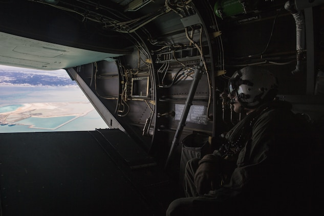 A crew chief looks out of the back of an MV-22B Osprey during helicopter support team training at Camp Foster, Okinawa, Japan, Jan. 14, 2019. Landing Support Company, 3rd Transportation Support Battalion, Combat Logistics Regiment 3, 3rd Marine Logistics Group supported Marine Medium Tiltrotor Squadron 265, Marine Aircraft Group 36, 1st Marine Aircraft Wing during external lift training, which ensures pilots and landing support specialists are able to communicate and transport gear from one location to another. (U.S. Marine Corps Photo by Cpl. André T. Peterson Jr.)