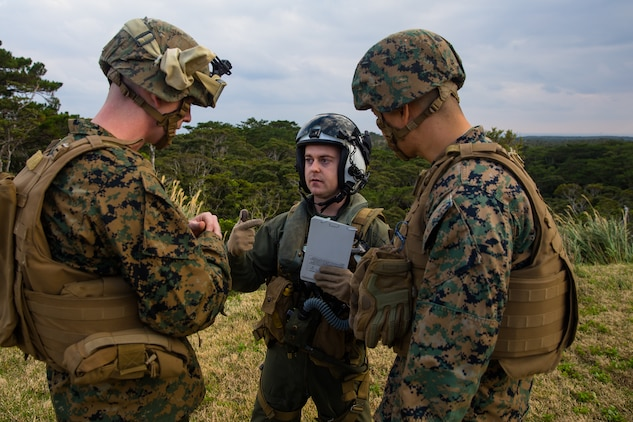 An MV-22B Osprey pilot speaks to landing support specialists during helicopter support team training at Camp Hansen, Okinawa, Japan, Jan. 14, 2019. Landing Support Company, 3rd Transportation Support Battalion, Combat Logistics Regiment 3, 3rd Marine Logistics Group supported Marine Medium Tiltrotor Squadron 265, Marine Aircraft Group 36, 1st Marine Aircraft Wing during external lift training, which provides valuable flight training hours for pilots as well as field training for LS Co. Marines. (U.S. Marine Corps Photo by Cpl. André T. Peterson Jr.)