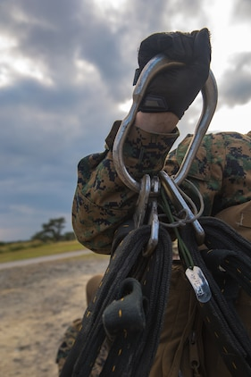 An apex ring connects a cargo net to an MV-22B Osprey's cargo hook during helicopter support team training at Camp Hansen, Okinawa, Japan, Jan. 14, 2019. Landing Support Company, 3rd Transportation Support Battalion, Combat Logistics Regiment 3, 3rd Marine Logistics Group supported Marine Medium Tiltrotor Squadron 265, Marine Aircraft Group 36, 1st Marine Aircraft Wing during external lift training, which provides valuable flight training hours for pilots as well as field training for Landing Support Company. (U.S. Marine Corps Photo by Cpl. André T. Peterson Jr.)