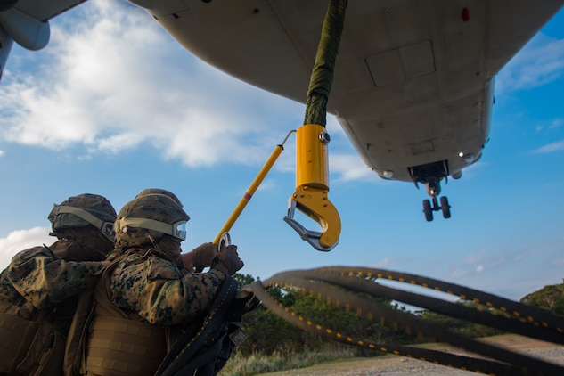 Landing support specialist attach an apex to an MV-22B Osprey hook during helicopter support team training at Camp Hansen, Okinawa, Japan, Jan. 14, 2019. Landing Support Company, 3rd Transportation Support Battalion, Combat Logistics Regiment 3, 3rd Marine Logistics Group supported Marine Medium Tiltrotor Squadron 265, Marine Aircraft Group 36, 1st Marine Aircraft Wing during external lift training, which ensures pilots and landing support specialists are able to communicate as well as transport gear from one location to another. (U.S. Marine Corps Photo by Cpl. André T. Peterson Jr.)