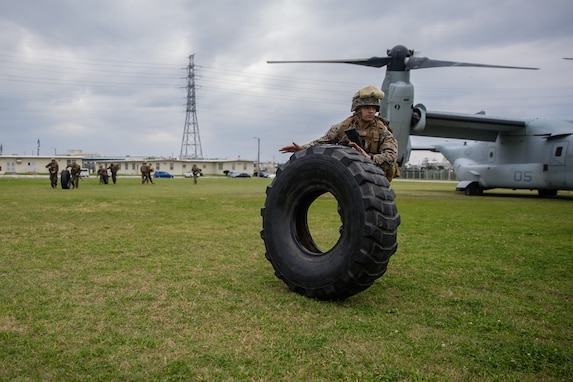 Lance Cpl. David S. Gutierrez rolls a Medium Tactical Vehicle Replacement tire during helicopter support team training at Camp Foster, Okinawa, Japan, Jan. 14, 2019. Landing Support Company, 3rd Transportation Support Battalion, Combat Logistics Regiment 3, 3rd Marine Logistics Group supported Marine Medium Tiltrotor Squadron 265, Marine Aircraft Group 36, 1st Marine Aircraft Wing during external lift training, which ensures pilots and landing support specialists are able to communicate and transport gear from one location to another. Gutierrez, a landing support specialist, is a native of El Paso, Texas. (U.S. Marine Corps Photo by Cpl. André T. Peterson Jr.)