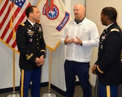 Three men talking. The two on the outside are wearing Army dress uniforms and the man in the middle is wear with top uniform from Honda and blue pants. Two flags in the background. The US flag and the Army Recruiting Flag.