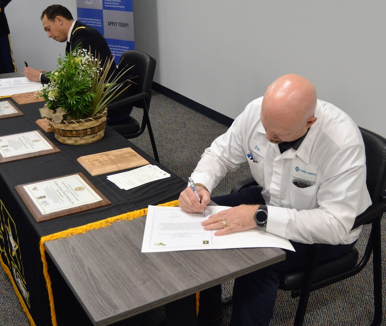 Two men sitting sign documents. One in white top from Honda and the other an Army soldier in dress blues. There is a plant in the middle of the table