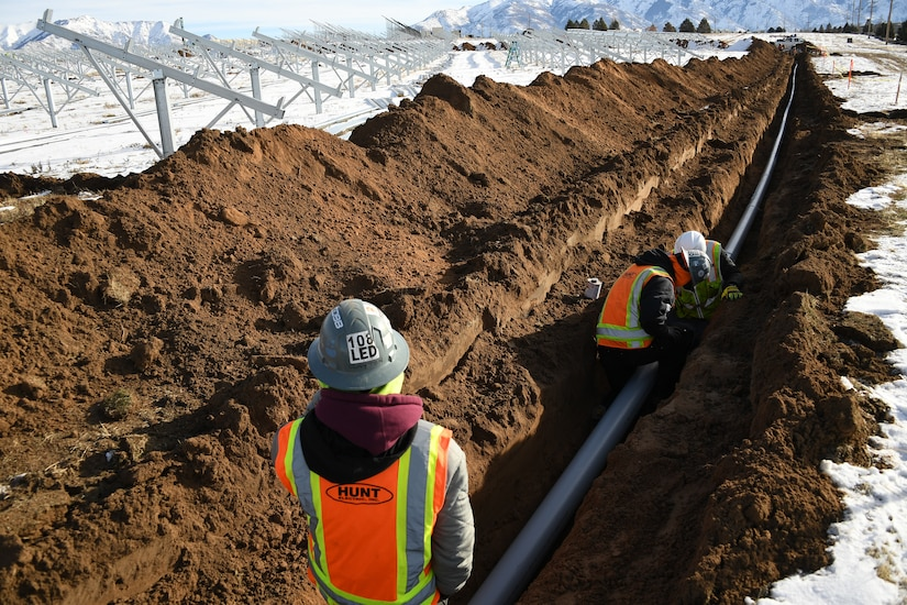 Workers in personal protective gear assemble a pipe inside a trench dug in a snowy field.