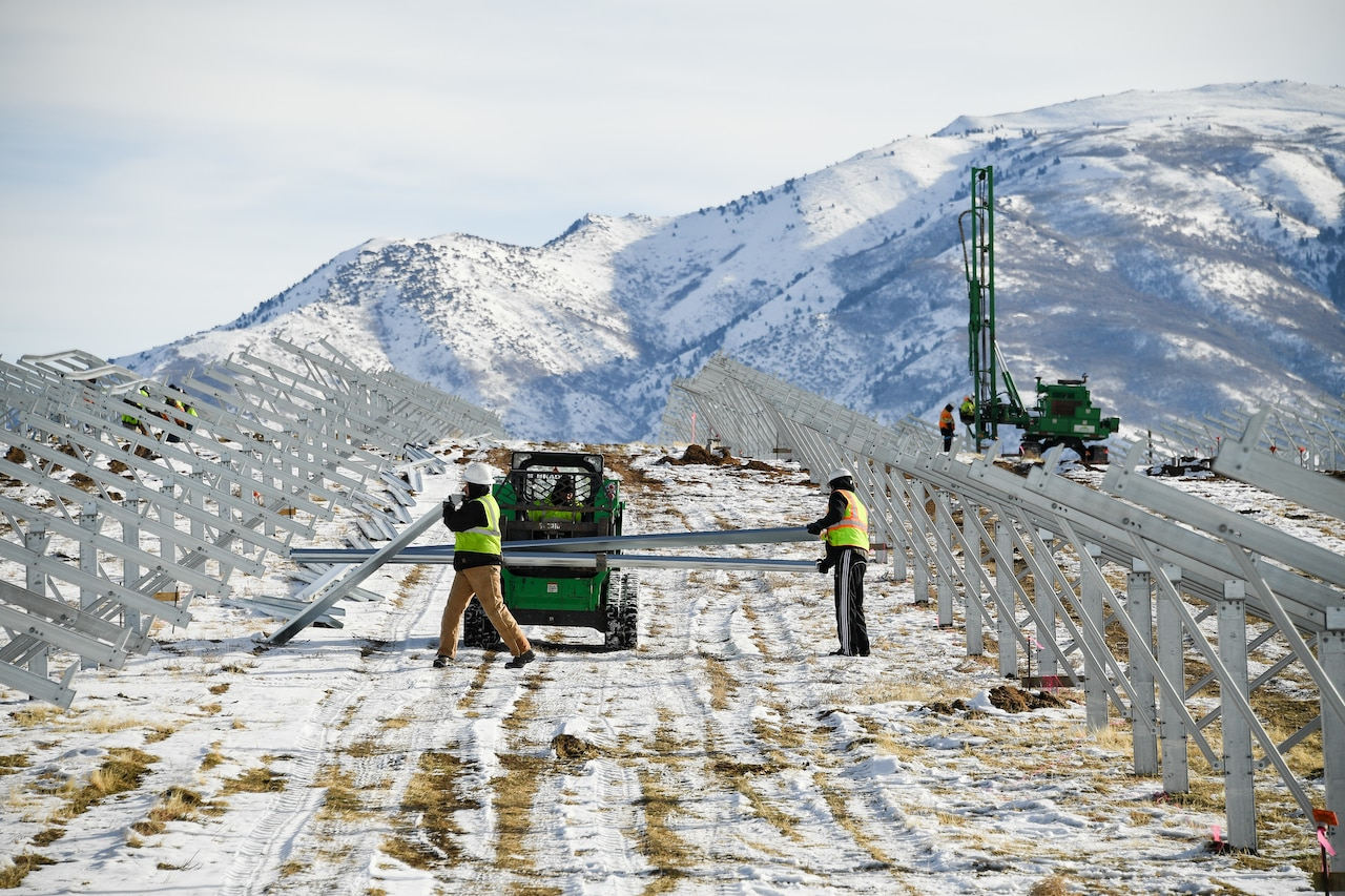 Workers in personal protective gear carry large metal brackets while building solar panels in a snowy field.