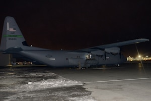 A C-130J in the dark surrounded by snow and ice.