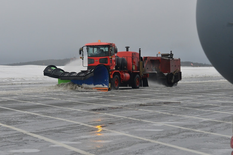 A plower plows ice and snow off a flightline.