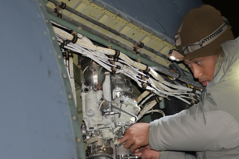 A man wearing a heavy winter coats fixes the inside of a C-130J.