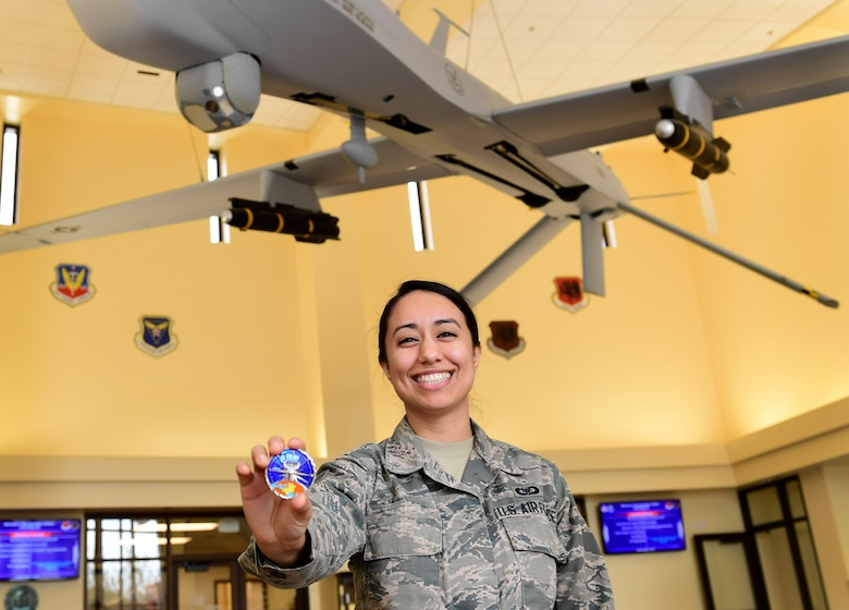 U.S. Air Force 78th Attack Squadron aviation resource manager, shows the coin she received from U.S. Air Force Lt. Gen. Joseph Guastella, U.S. Air Forces Central Command commander, at Creech Air Force Base, Nevada, Jan. 16, 2019. Guastella coined several 432nd Wing/432nd Expeditionary Wing and 799th Air Base Group outstanding Airmen. (U.S. Air Force photo by Senior Airman Christian Clausen)